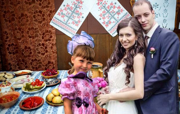 Перед свадебным праздничным столом жених, невеста и ее дочь.